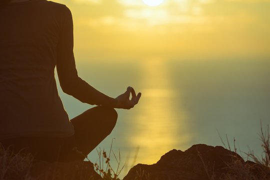 Woman meditating and relaxing her mind in a beautiful sunset setting.