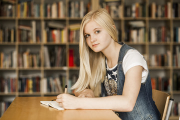 Teenage girl studying at desk in library