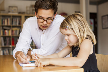 Father assisting daughter doing homework