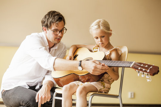 Male teacher assisting girl playing acoustic guitar