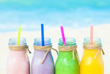 Assortment of mixed fruit shakes on the beach.