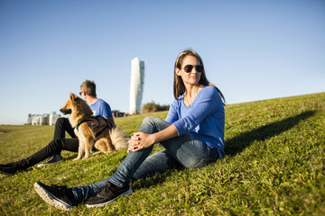 Couple with dog relaxing on grassy slope with Turning Torso skyscraper in background