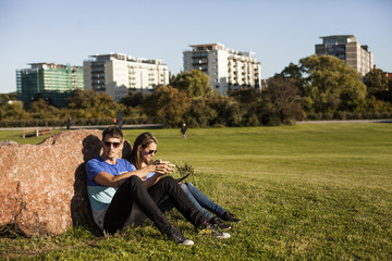 Couple sitting at park in city against clear sky