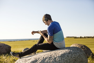 Side view of man using mobile phone while listening music on rock against clear sky