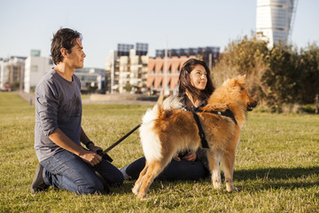 Multi-ethnic couple with dog relaxing at park in city