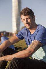 Portrait of smiling man sitting at park with Turning Torso skyscraper in background