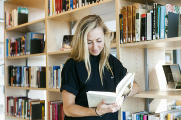 Young woman reading book while leaning on bookshelf in college library