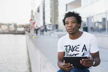 Thoughtful male college student holding digital tablet while sitting on retaining wall by river