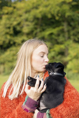 Young woman kissing puppy outdoors