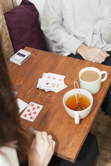 Cropped image of couple playing cards at table in coffee shop
