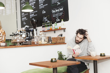 Mid adult man reading book at cafeteria