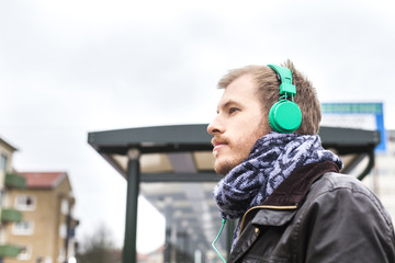 Side view of man listening music at bus stop against clear sky