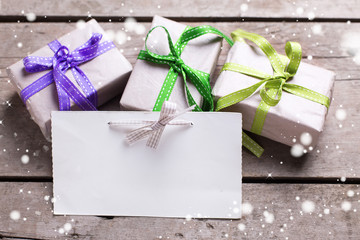 Empty tag and three festive gift boxes with presents on vintage