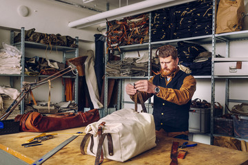 Male worker attaching leather belt to bag at worktable in factory