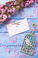 Background  with pink flowers and empty tag on blue wooden plank