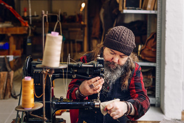 Man sewing in leather shop