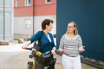 Mature female friends talking while walking with bicycle on street