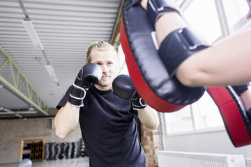 Young man with trainer practicing boxing in health club