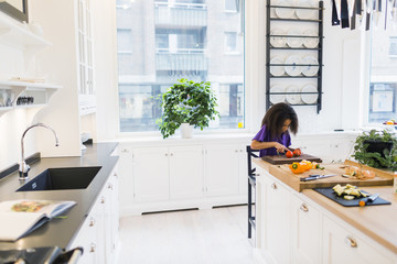 Girl slicing tomatoes in kitchen