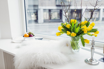 Fur rug and flower vase on window sill