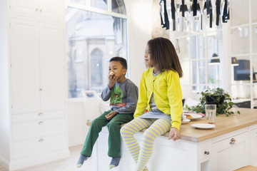 Brother and sister sitting on kitchen island
