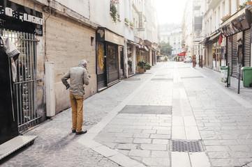 Rear view of senior man standing on sidewalk amidst buildings