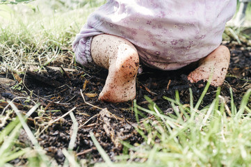 Low section of baby with dirty feet kneeling on dirt