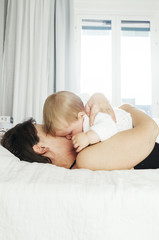 Woman hugging baby in bed at home