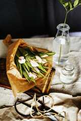 Tulip bouquet on chopping board by vases on table