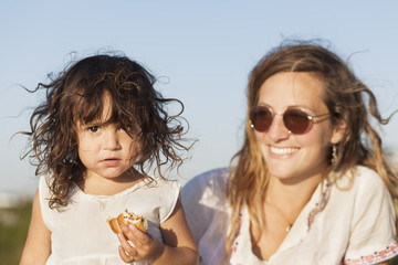 Portrait of cute girl holding food while mother looking at her in park