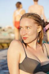 Sensuous young woman in bikini looking away while sitting on pier