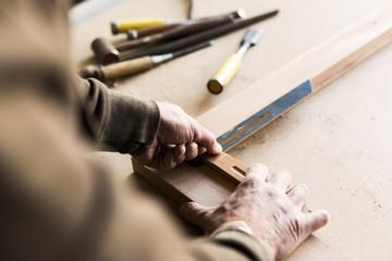 Cropped image of carpenter using sliding T bevel in workshop