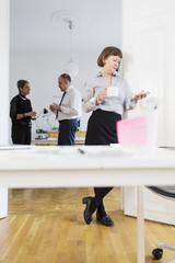 Businesswoman with mobile phone and coffee cup against colleagues discussing in office