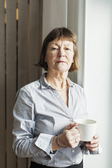 Portrait of senior businesswoman holding coffee cup in office