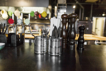 Pepper grinders and cutlery on kitchen counter