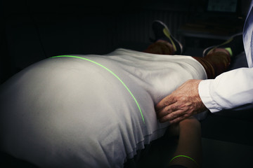Cropped image of doctor measuring the person's stomach through laser machine