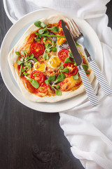 Home Italian pizza with tomato and quail eggs salad on a white p