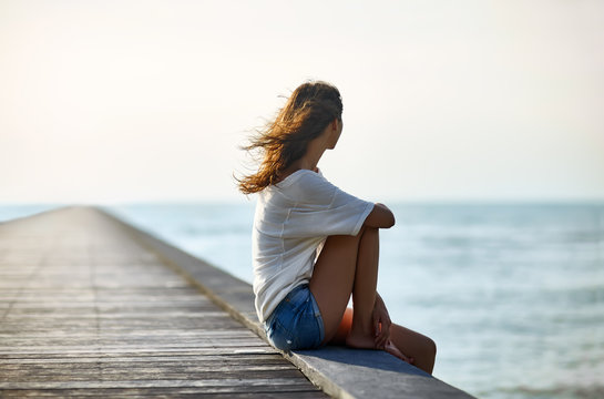 Young beautiful woman sitting on the pier