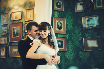 Bride stands with closed eyes while groom holds her waist tender