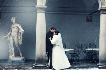Picture in blue tones of newlyweds kissing behind a pillar while