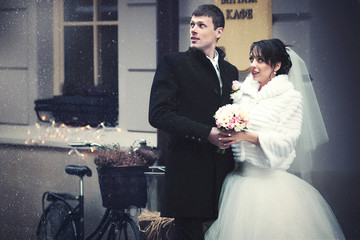 Bride and groom look in the sky standing behind an old bicycle