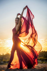 Girl in airy dress posing at sunset