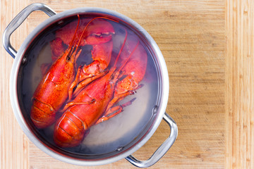 Two red lobsters in a pot of boiling water