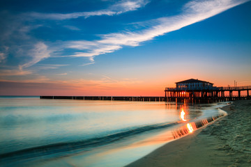 Restaurant at wooden pier on the baltic sea during sunrise. Ustronie Morskie, Poland.