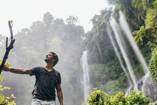 Young man standing near a waterfall in forest