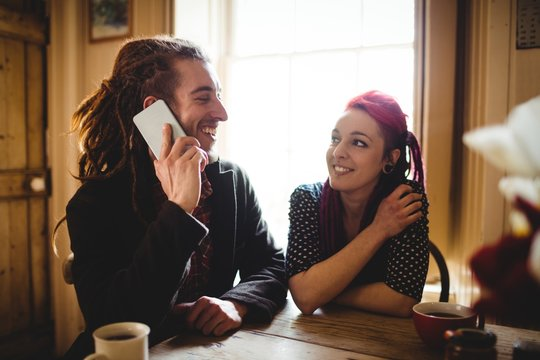 Man talking on phone while sitting by woman
