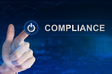 business hand clicking compliance button