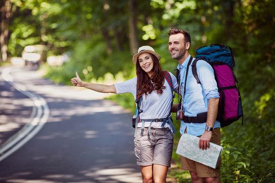 Happy couple hitchhiking