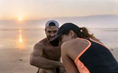 Spain, Aviles, athletes couple training on the beach at sunset