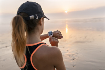 Young athlete woman looking the smartwatch on the beach at sunset
